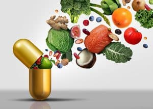 Vitamins Supplements As A Capsule With Fruit Vegetables Nuts And